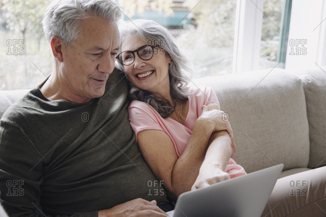Happy senior couple with laptop relaxing on couch at home