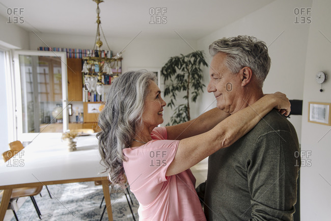 Happy senior couple embracing in living room at home