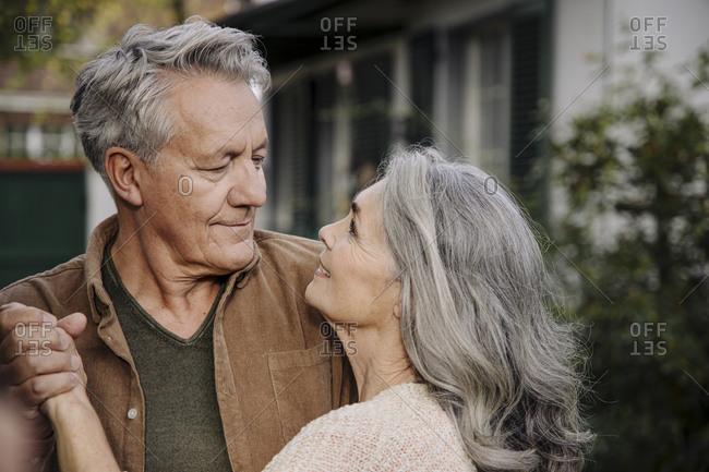 Affectionate senior couple in garden of their home in autumn