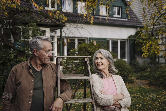 Senior couple with a ladder in garden of their home