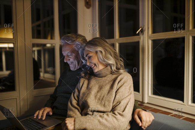 Senior couple using laptop on couch at home at night