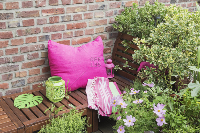 Balcony with bench- pink cushion- blanket- lanterns and various potted plants