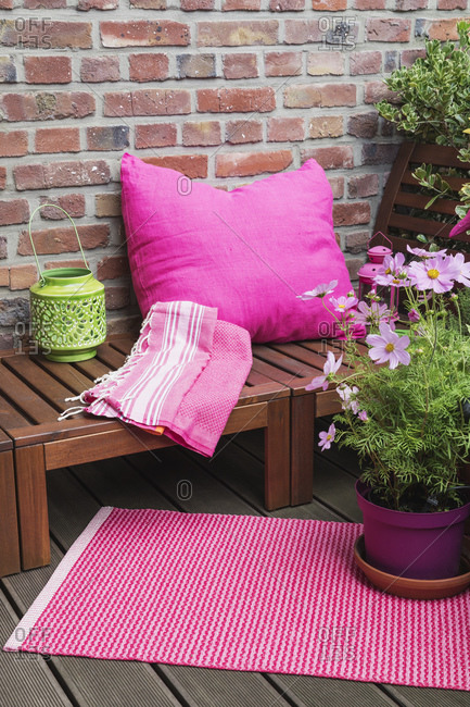 Balcony with bench- pink cushion- blanket- lantern- mat and various potted plants