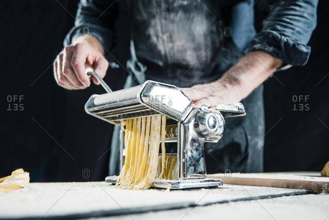 Hobby chef making fresh tagliatelle with pasta machine
