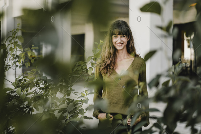 Portrait of smiling brunette woman behind plants
