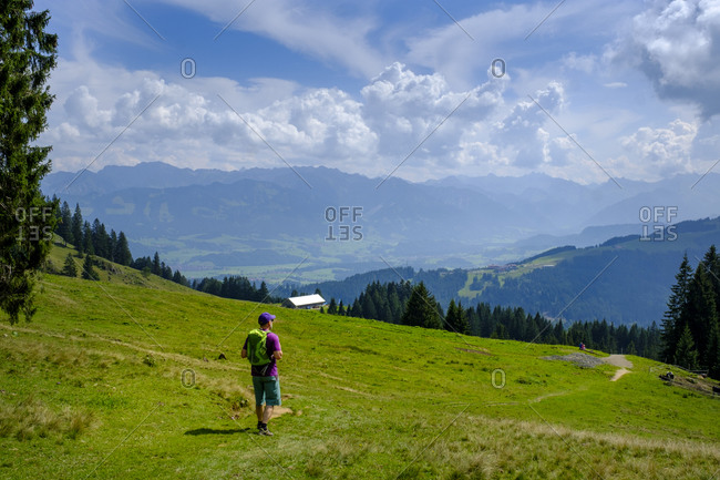 Germany- Bavaria- Immenstadt- Lone hiker taking break to admire scenic landscape of Allgau Alps