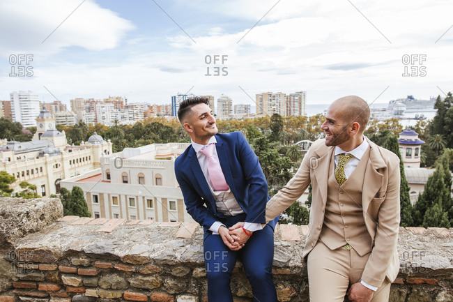 Elegant gay couple holding hands at an observation point above the city- Malaga- Spain