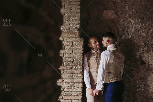 Affectionate elegant gay couple in an old building