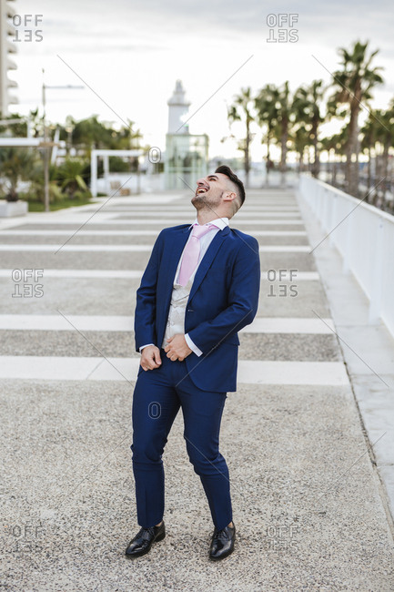 Elegant man standing on a promenade laughing