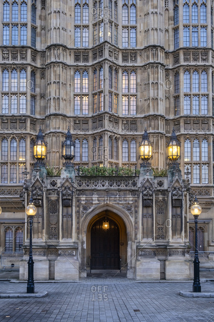 UK- England- London- Street lights glowing in front of Palace of Westminster entrance at dusk
