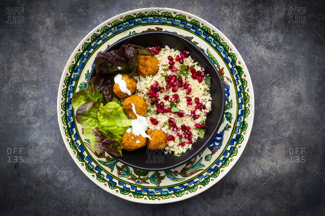 Bowl of falafel with lettuce- yogurt- pomegranate seeds- parsley- mint and Tabbouleh salad