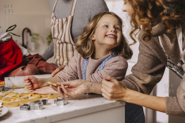 Happy family preparing Christmas cookies in kitchen