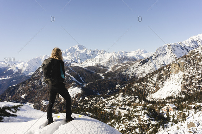 Woman standing with snowshoes on viewpoint- Valmalenco- Italy