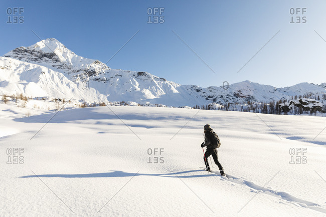 Woman walking with snowshoes in fresh snow in the mountains- Valmalenco- Italy