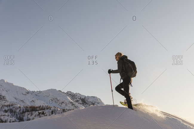 Woman walking with snowshoes in fresh snow in the mountains at sunset- Valmalenco- Italy