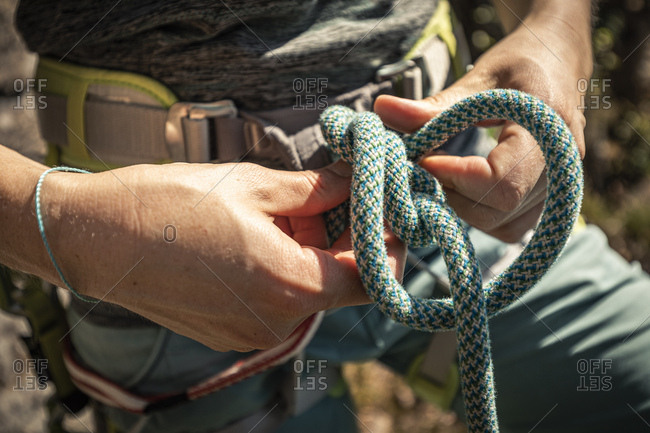 Woman preparing to climb- checking rope- figure eight knot