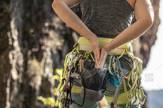 Woman preparing to climb- using chalk powder