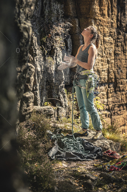 Woman preparing to climb- looking up on climbing wall