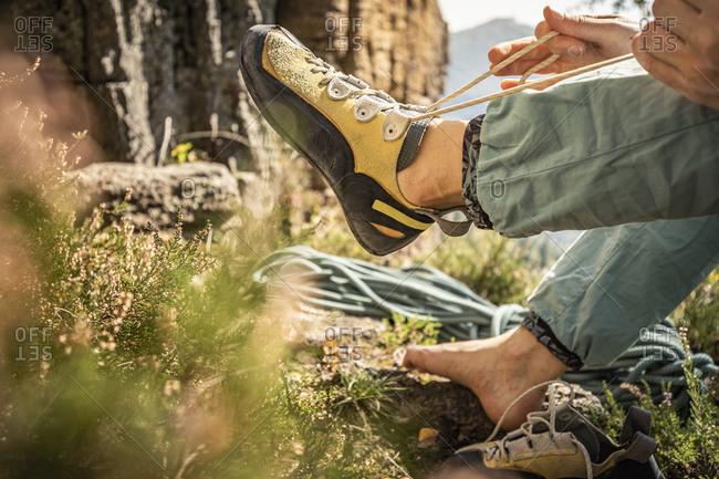 Woman preparing to climb- tying climbing shoe