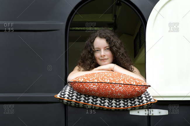 Portrait of young woman leaning on cushions looking out of caravan