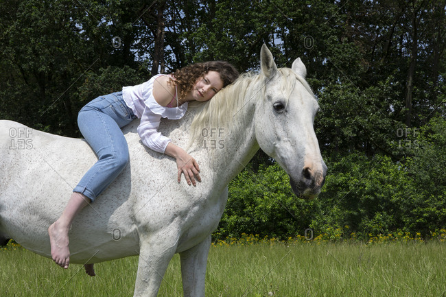 Portrait of young woman sitting bareback on a horse
