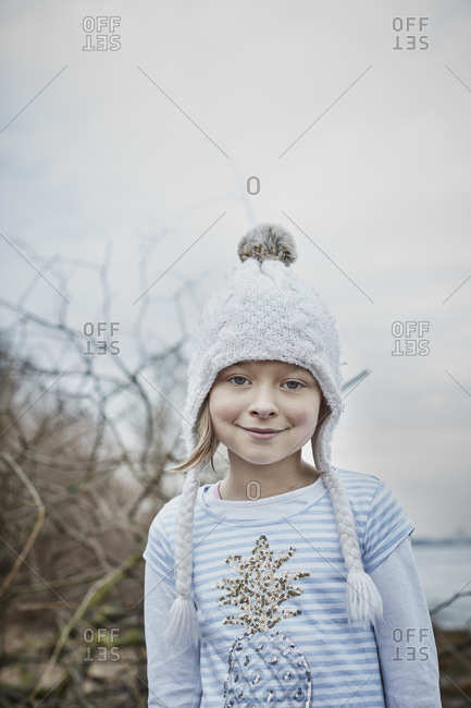 Portrait of smiling little girl wearing bobble hat in nature