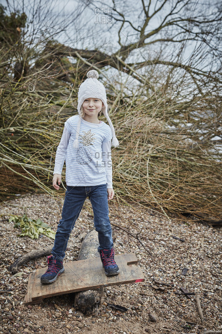 Portrait of smiling little girl wearing bobble hat balancing on seesaw