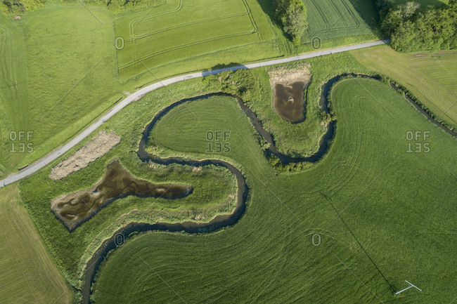 Germany- Bavaria- Aerial view of green countryside fields and meandering Wornitz river