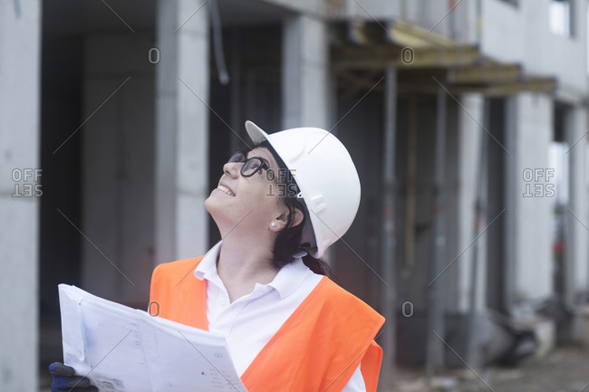 Female construction engineer looking up- holding construction plan