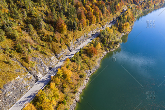 Germany- Bavaria- Lenggries- Aerial view of empty highway stretching along shore of Sylvenstein Reservoir in autumn