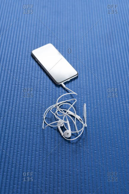 Smartphone and earphones on blue workout mat