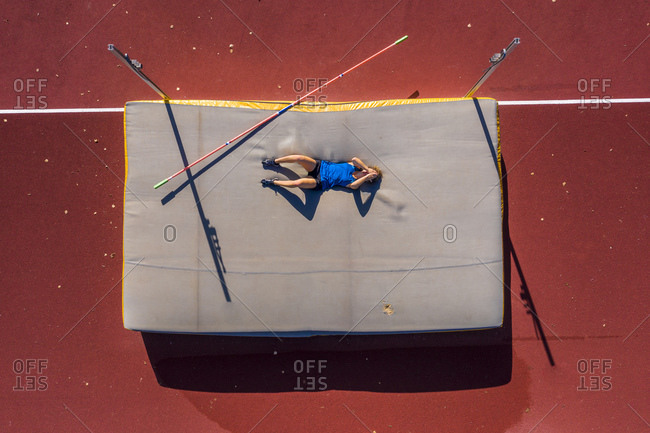 Germany- Baden-Wurttemberg- Winterbach- Female athlete lying on mat after failed high jump