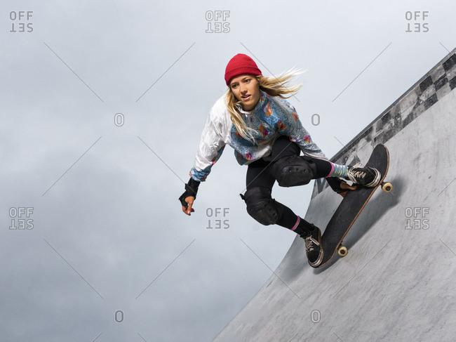 Germany- Baden-Wurttemberg- Waiblingen- Young woman skateboarding in skate park