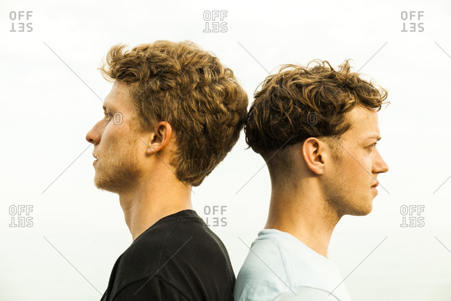 Portrait of strawberry blonde young men- back to back