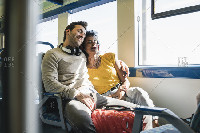 Young couple with closed eyes relaxing in a train