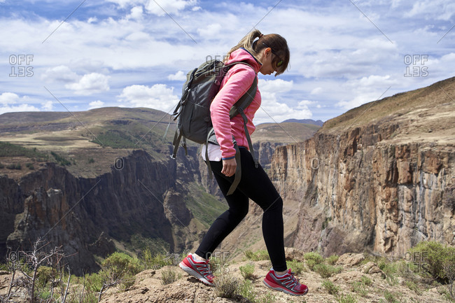 Woman hiking on top of a hill at Maletsunyane Falls- Lesotho