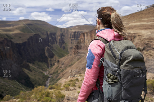 Woman standing on top of a hill at Maletsunyane Falls enjoying the view- Lesotho
