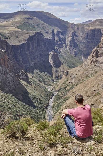 Man sitting on top of a hill at Maletsunyane Falls enjoying the view- Lesotho