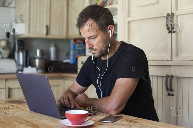 Man working from home- sitting at kitchen table- using laptop and smartphone