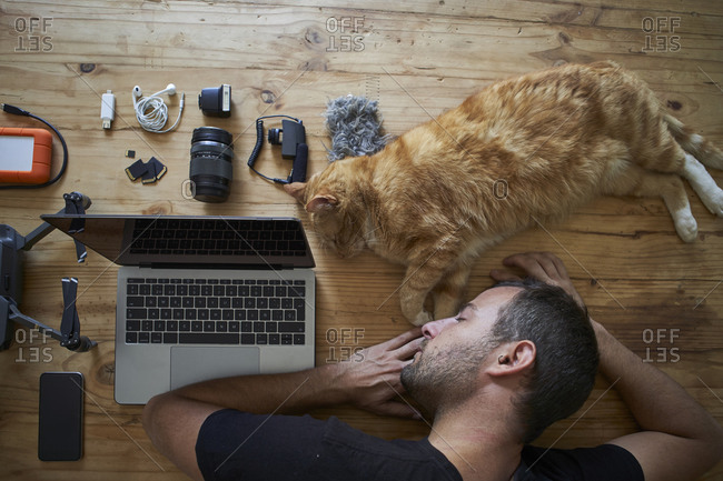 Exhausted man sleeping on table with ginger cat- laptop and photographic equipment