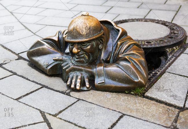 October 5, 2008: Slovakia- Bratislava- Bronze sculpture of man in manhole
