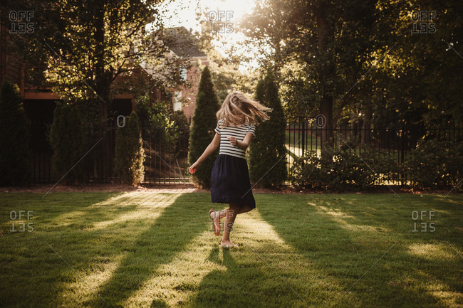 Girl spinning in yard
