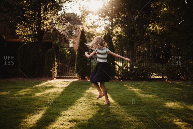 Girl twirling in yard