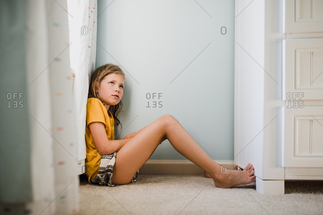 Girl sitting in a corner pouting