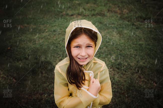 Portrait of a girl wearing yellow rain jacket in the rain