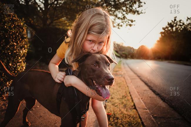 Girl kissing her dog on street side of residential area