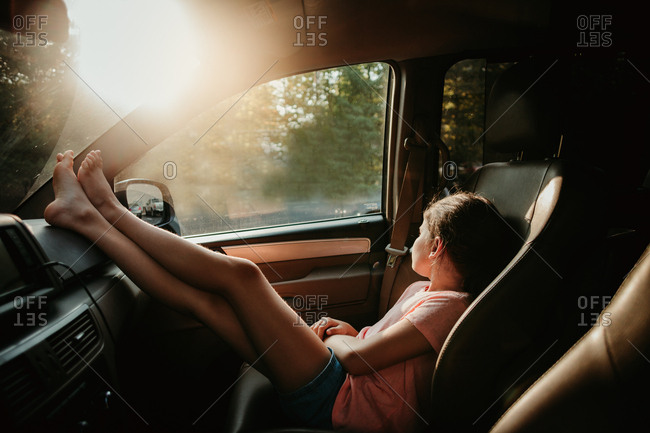 Girl resting feet on dashboard while waiting in a car