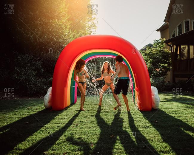 Kids playing in rainbow sprinkler