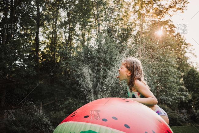 Girl drinking from a sprinkler