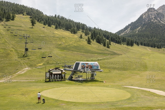 Montgenevre, France - July 18, 2019: Golfer playing on course by ski lift in the French Alps